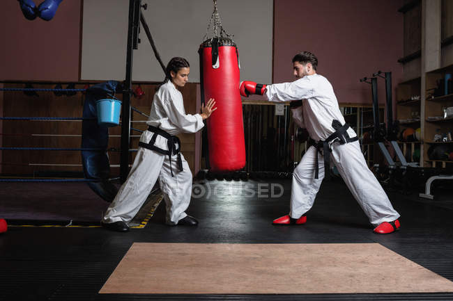 Side view of strong sportswoman and sportsman practicing karate with punching bag in studio — Stock Photo