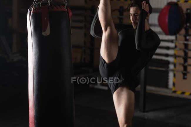 Boxer übt Boxen mit Boxsack im Fitnessstudio — Stockfoto