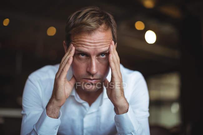 Primer plano del empresario tenso sentado con la mano en el templo - foto de stock