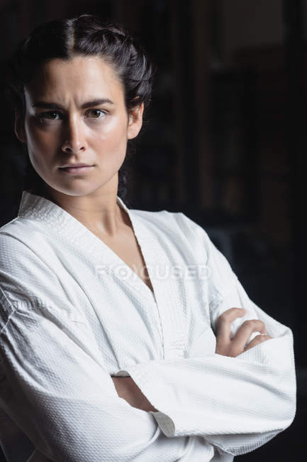 Portrait of woman in karate kimono standing with crossed arms in fitness studio and looking at camera — Stock Photo