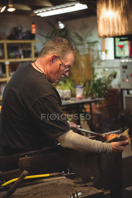 Glasbläser formen mundgeblasenes Glasstück mit feuchtem Tuch in Glasbläserei — Stockfoto