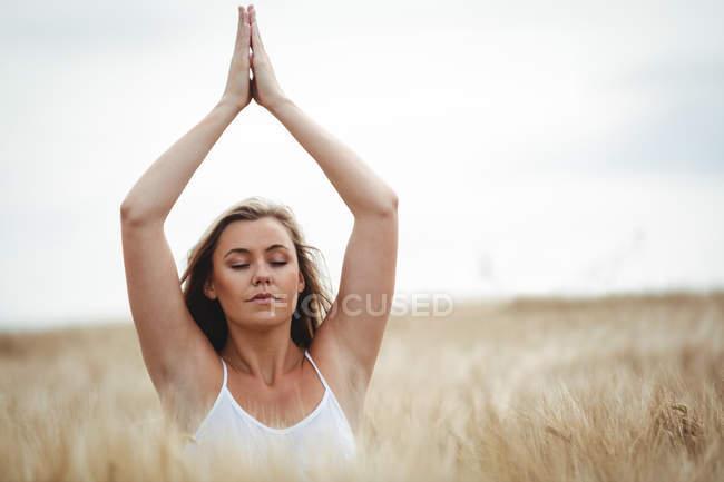 Femme avec les mains levées sur la tête en position de prière dans le champ par une journée ensoleillée — Photo de stock