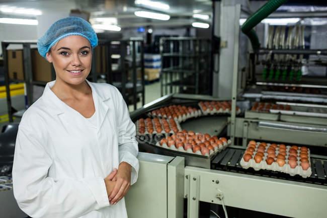 Сотрудницы стоя рядом с конвейера на заводе яйцо — стоковое фото