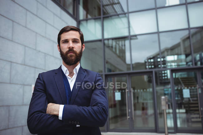 Portrait of businessman standing with arms crossed outside office — Stock Photo