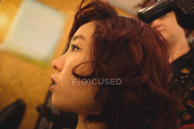 Coup de styliste de cheveux sécher les cheveux de la femme dans un salon professionnel — Photo de stock