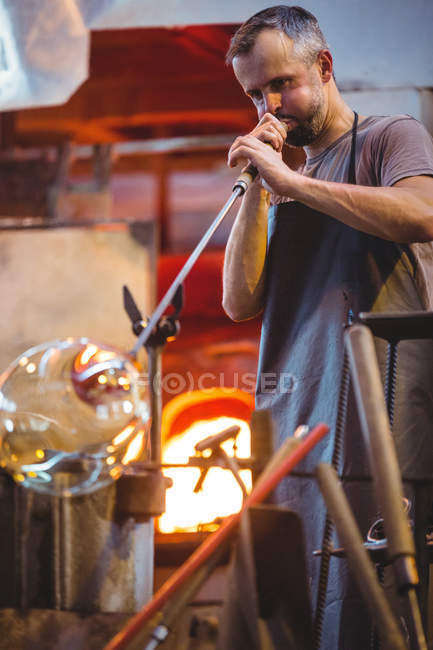 Glassblower shaping a glass on the blowpipe at glassblowing factory — Stock Photo