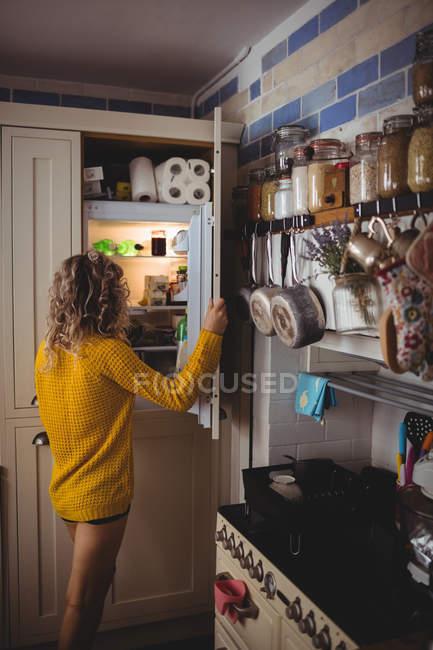 Женщина ищет еду в холодильнике на кухне дома — стоковое фото