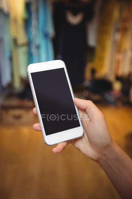 Hand of woman using mobile phone in apparel store — Stock Photo