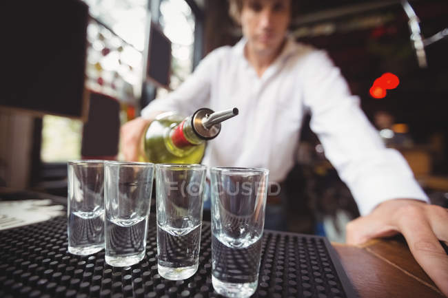 Close-up of bartender pouring tequila in shot glasses on bar counter at bar — Stock Photo