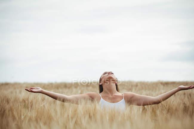 Frau mit ausgestreckten Armen im Feld — Stockfoto