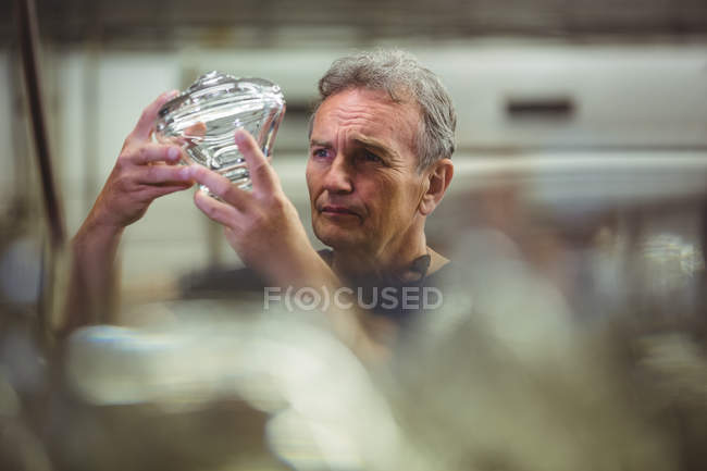 Glassblower examining glassware at glassblowing factory — Stock Photo