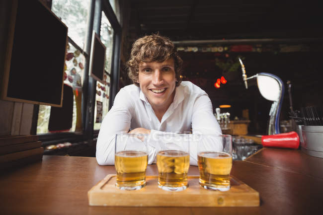 Portrait of bartender with tray of whisky shot glasses at bar counter in bar — Stock Photo