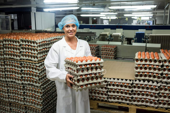 Portrait of female staff holding egg trays in factory — Stock Photo