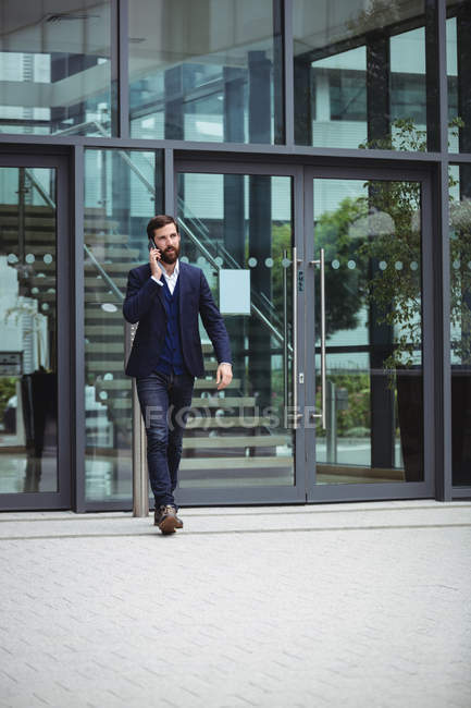 Businessman talking on mobile phone outside office — Stock Photo
