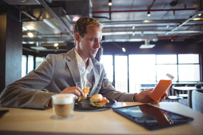 Businessman having breakfast in cafeteria during office hours — Stock Photo