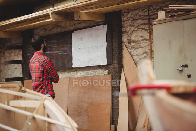 Rear view of man looking at blueprint in boatyard — Stock Photo