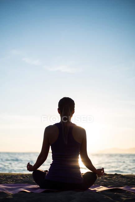 Вид сзади женщины, практикующей йогу на пляже во время заката — стоковое фото