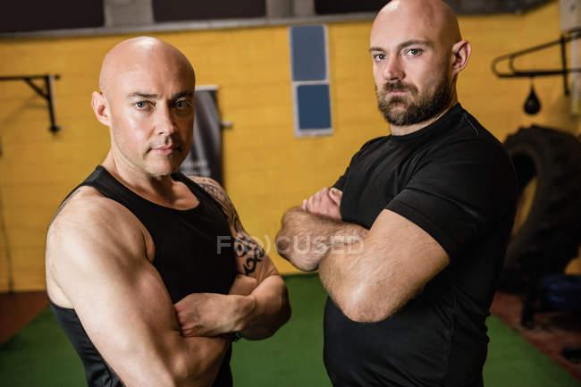 Portrait de boxeurs thaïs confiants debout avec les bras croisés dans un studio de fitness et regardant la caméra — Photo de stock