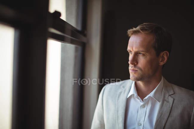 Uomo d'affari premuroso che guarda attraverso la finestra in ufficio — Foto stock