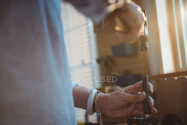 Mid-section of craftswoman using hammer in workshop — Stock Photo