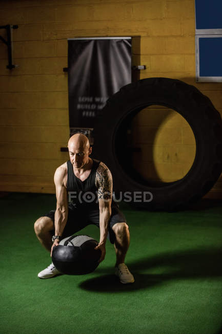 Handsome tattooed sportsman lifting weight in gym — Stock Photo