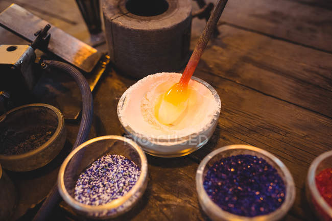 Close-up of attaching colored glass to a piece of hot molten glass at glassblowing factory — Stock Photo