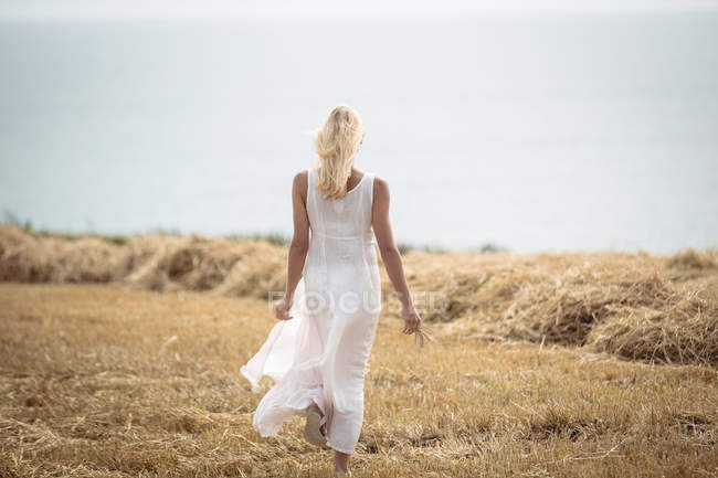 Back view of carefree blonde woman walking in field near river — Stock Photo