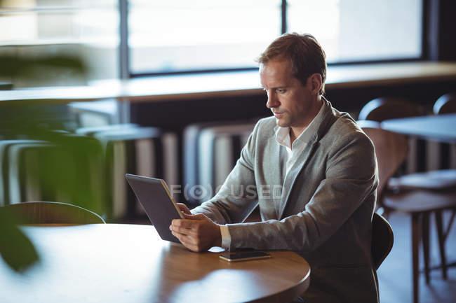 Uomo d'affari concentrato utilizzando tablet digitale in caffè — Foto stock