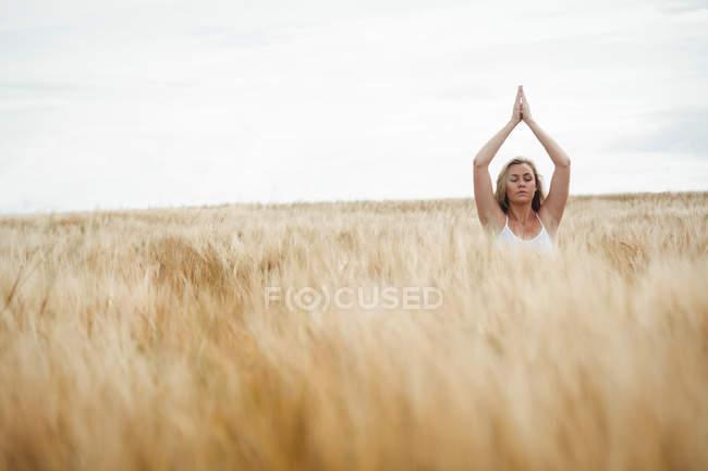 Женщина с поднятыми над головой руками в молитвенном положении на поле в солнечный день — стоковое фото
