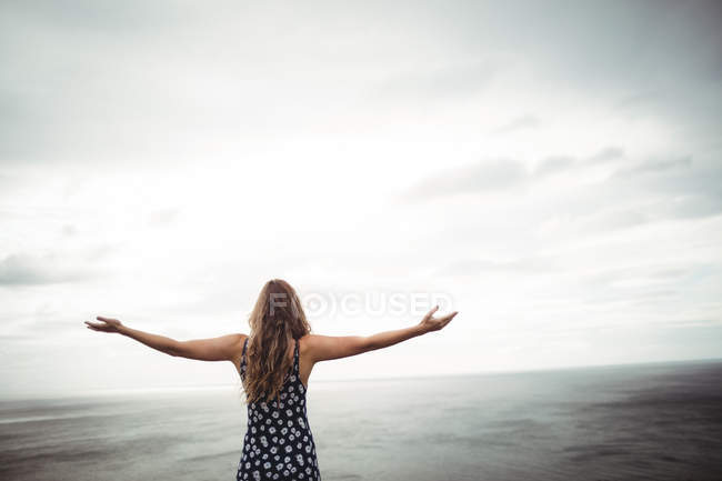 Rear view woman standing with arms outstretched on cliff over sea — Stock Photo