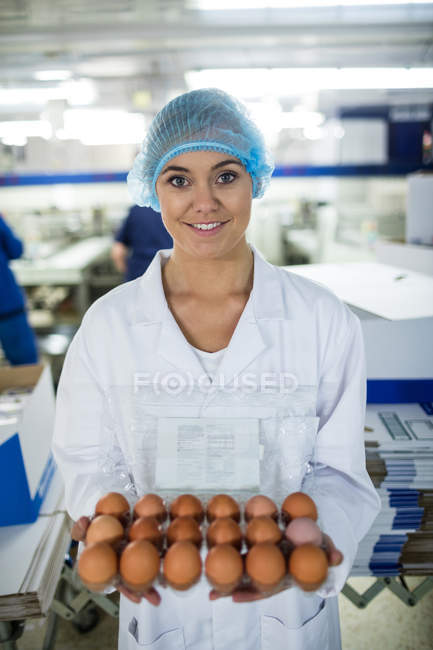 Portrait of female staff holding egg tray in factory — Stock Photo