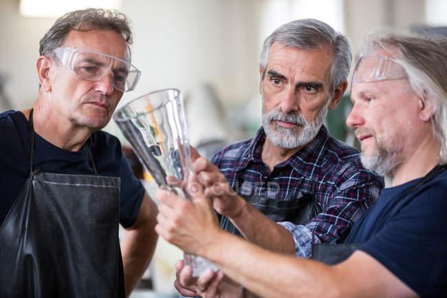 Стеклодувы, взаимодействующие при исследовании стеклянной вазы на стекольном заводе — стоковое фото