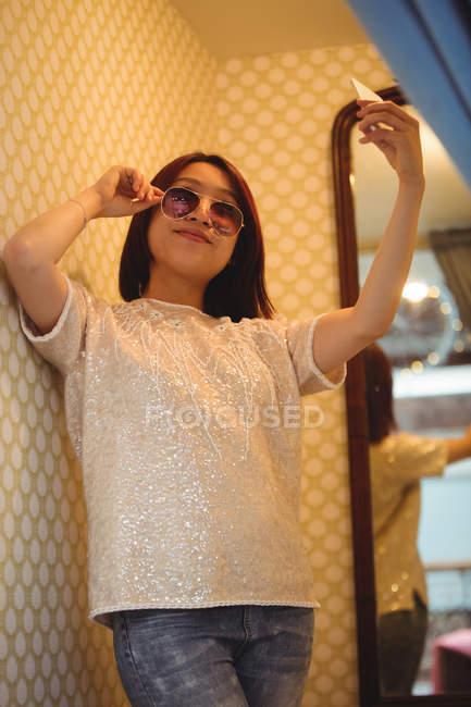 Женщина делает селфи с мобильного телефона в бутик-магазине — стоковое фото