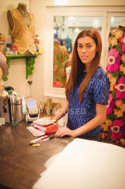 Female staff standing at a counter in boutique store — Stock Photo