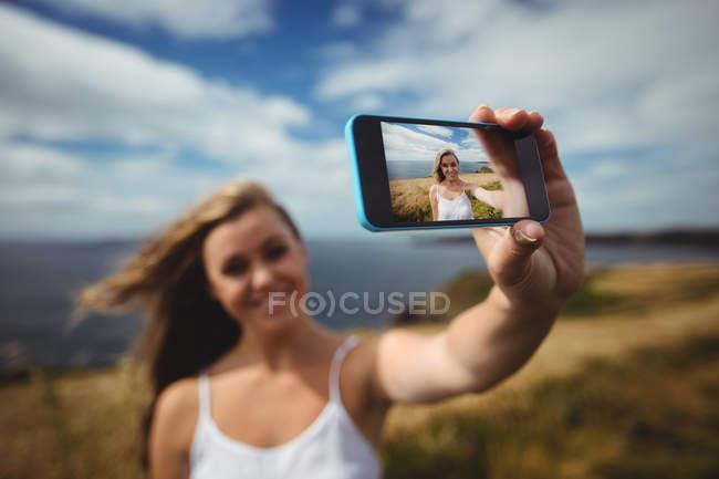Femme souriante tenant selfie smartphone dans le champ — Photo de stock