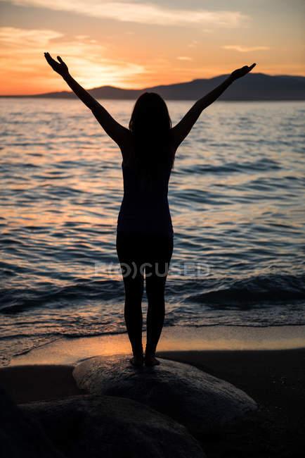 Vue arrière de la femme pratiquant le yoga sur la roche à la plage pendant le coucher du soleil — Photo de stock