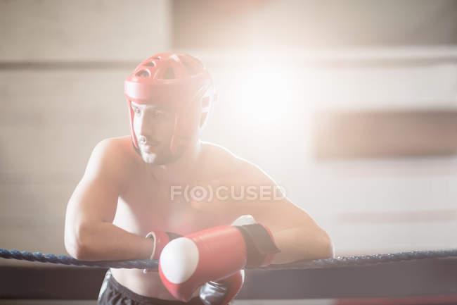 Боксер в захисних шоломи боксерські спираючись на тросах боксерський ринг в фітнес-студія — стокове фото