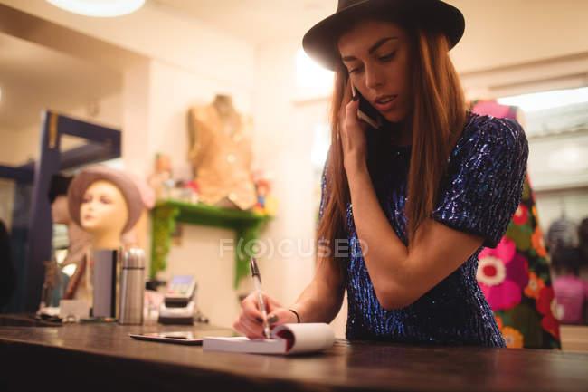 Personal femenino tomar orden en teléfono móvil en boutique tienda - foto de stock