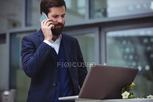 Бизнесмен разговаривает по мобильному телефону во время использования ноутбука — стоковое фото
