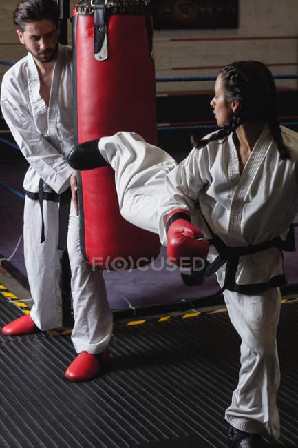 Kämpferinnen und Kämpfer üben Karate mit Boxsack im Studio — Stockfoto