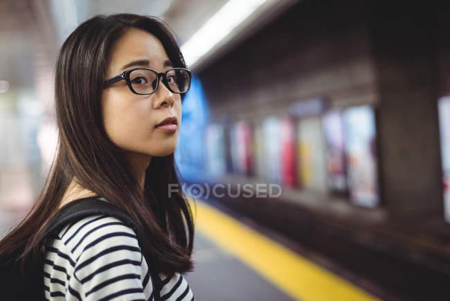 Молодая женщина ждет поезд на железнодорожном вокзале — стоковое фото