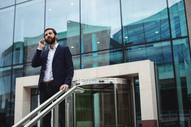 Businessman talking on mobile phone at the entrance of office building — Stock Photo