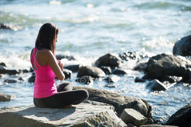 Frau meditiert im Lotus und posiert an sonnigen Tagen auf einem Felsen — Stockfoto