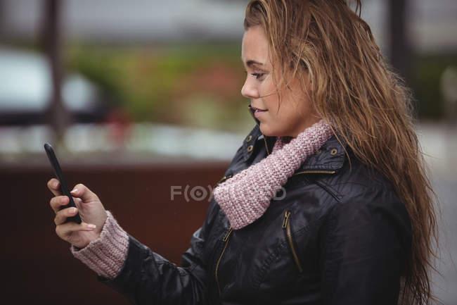 Vue latérale de Belle femme portant une veste en cuir et utilisant un smartphone sur la rue — Photo de stock