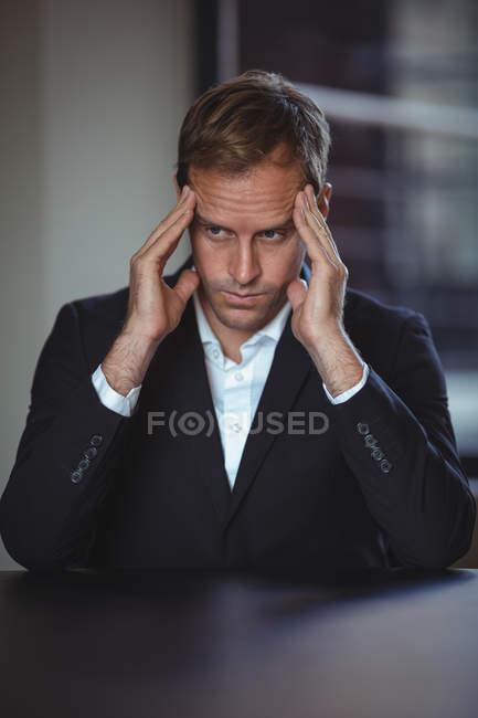 Empresário tenso sentado no escritório com a mão em templos — Fotografia de Stock