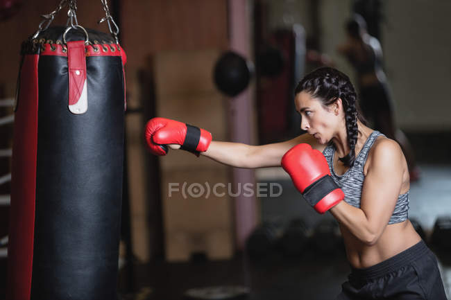 Seitenansicht einer Boxerin beim Boxen mit Boxsack im Fitnessstudio — Stockfoto