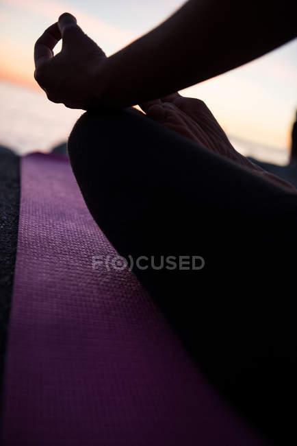 Immagine ritagliata di donna seduta in posizione loto con gesto mudra sulla spiaggia al crepuscolo — Foto stock