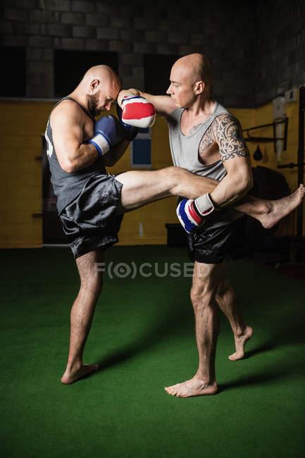 Vue latérale de deux boxeurs thaïlandais combattant dans la salle de gym — Photo de stock