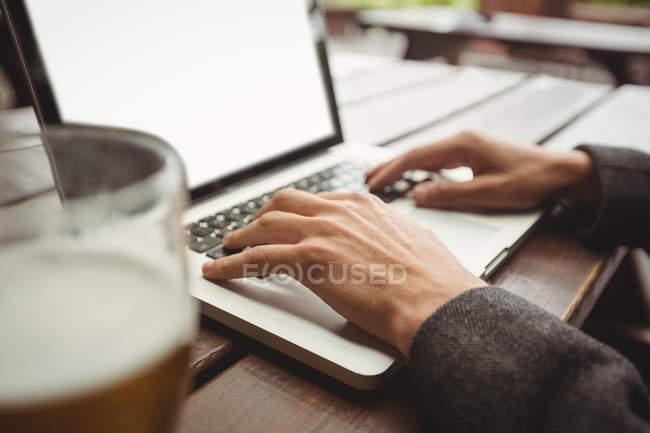 Close-up de homem usando laptop no bar — Fotografia de Stock