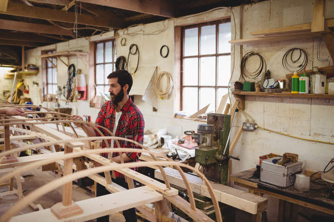 Man preparing a wooden boat frame at boatyard — Stock Photo